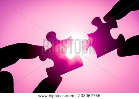 Silhouette Of Closeup Woman's Hand Connecting A Piece Of Jigsaw Puzzle Over Sunlight Effect. Symbol