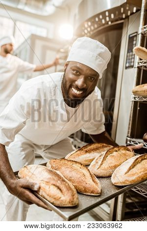 Happy African American Baker Taking Bread Loaves From Oven At Baking Manufacture