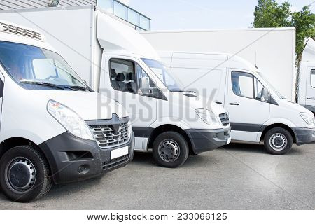 Several White Row Commercial Delivery Vans And Service Van, Trucks And Car In Front Of Factory Wareh