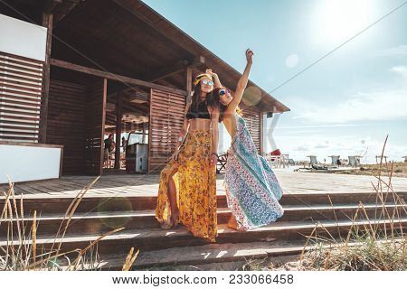 Two boho friends (girls) wearing floral maxi dress and skirt relaxing on the beach. Bohemian clothing style.
