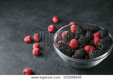 Glass Plate With Ripe Red Blackberries And Raspberries On A Black Surface. Macro Photo Of Ripe Black