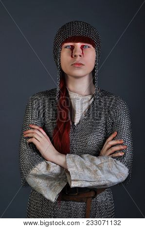 Medieval Girl In Chain Mail With Red Hair Stands On A Gray Background With Blood On Her Hands