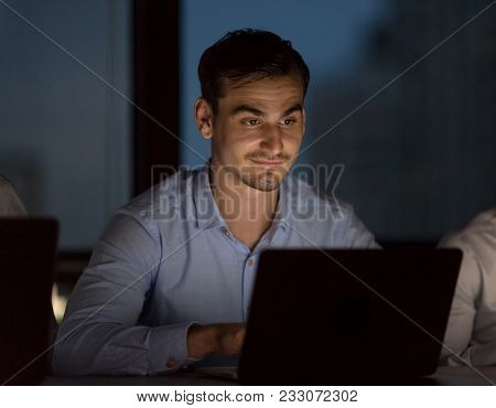 Handsome Businessman Working With Team Untill Late Night In Low Light From Laptop Screen With Blurre