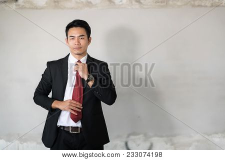 Young Handsome Asian Businessman Dressing Up With Red Necktie .