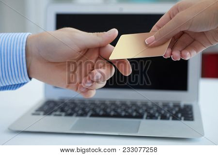 Closeup Shot Of A Woman's Hand Giving A Payment Credit Card To The Seller In Computer Store.