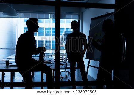 Silhouette Of Young Business People Discussing About Their Business Plan At Modern Startup Office. M
