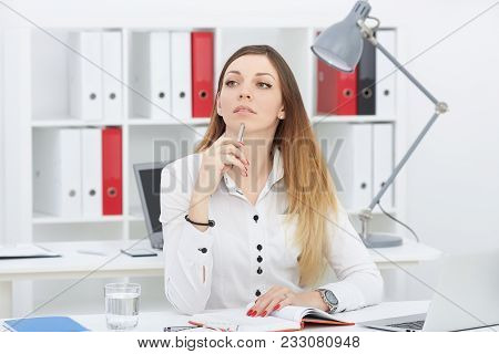 Beautiful Young Busines Woman Is Looking Into The Distance, Sitting At Her Workplace.