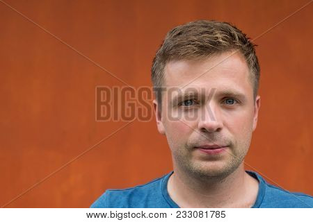 Simple Portrait Of Caucasian Man On Orange Background. Face Without Emotions