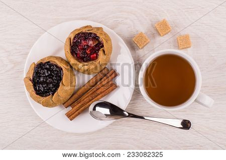 Pies With Cowberries And Blueberries, Cinnamon Sticks In Plate, Sugar, Cup Of Tea And Spoon On Woode