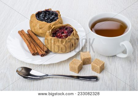 Pies With Cowberries And Blueberries, Cinnamon Sticks In Plate, Brown Sugar, Tea In Cup, Spoon On Wo