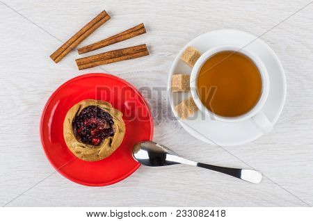 Pie With Cowberries In Red Saucer, Cinnamon Sticks, Spoon, Cup Of Tea, Sugar On Wooden Table. Top Vi