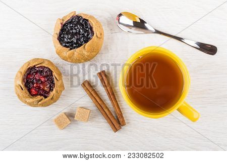 Pies With Blueberries, Cowberries, Sugar, Cinnamon, Tea In Cup, Spoon On Wooden Table. Top View
