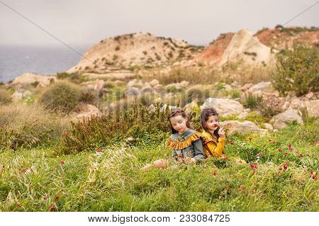 On The Grass Plateau Sit Two Sisters Girls In Retro Clothes Are Considered Sniffing Flowers With Hil