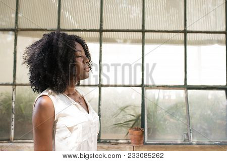 Calm Black Woman Standing With Closed Eyes Outdoors With Greenhouse In Background. Afro American Wal