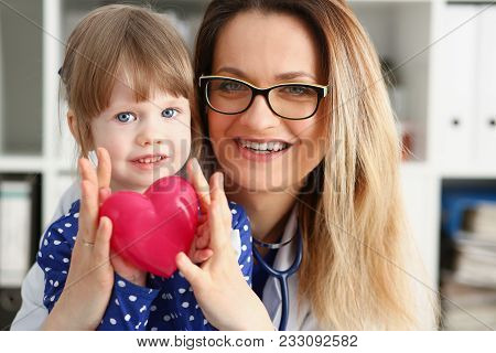 Female Doctor And Happy Little Child Hold In Arms Red Toy Heart Closeup. Cardio Therapeutist Student
