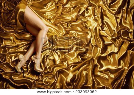 Woman Leg On Gold Silk Fabric Background, Sexy Fashion Model Legs In Golden Shoes Lying Over Waving