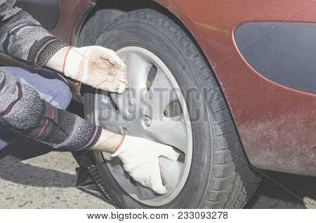 A Man Is Changing A Wheel In His Car On The Side Of The Road