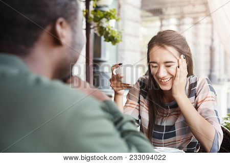 Young Bored Girl Sitting And Using Smartphone On Date With Her Boyfriend At Cafe. Speed Dating, Unsu