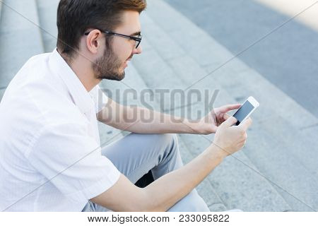 Young Smiling Businessman In Eyeglasses Texting On Cell Phone While Sitting On Stone Stairs, Closeup