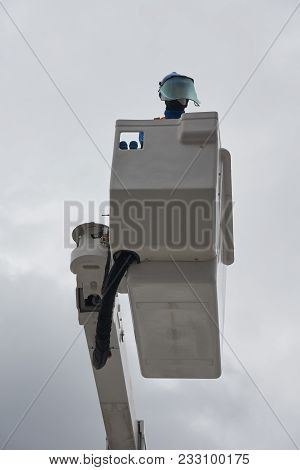 An Electrician (dummy) In Protective Uniform Works On Insulated Aerial Platform Designed To Work Saf