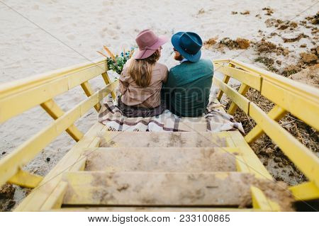Stylish Couple In Hats Sits On The Stairs Look At Each Other With Tenderness And Love. Rear View. Ar