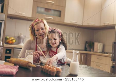 Young Mother In The Kitchen Baking Dough With Her Daughter, Daughter Reaching For An Egg While Mothe