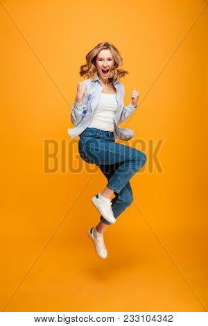 Full length picture of content ecstatic adult girl expressing delight and clenching fists isolated over yellow background