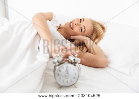 Close up of a happy young woman turning alarm off in the morning while lying in bed