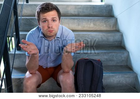 A Young Man Is Sitting On The Stairs And Sad. He Lost The Keys To The Apartment, Or He Was Kicked Ou