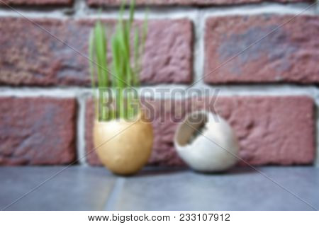 Defocused And Blurry Background With Golden Eggs And Growing Fresh Green Grass On Brick Wall, Freshn