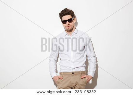 Portrait of fashion young man dressed in shirt and sunglasses posing on camera with hands in pockets over white background with shadow