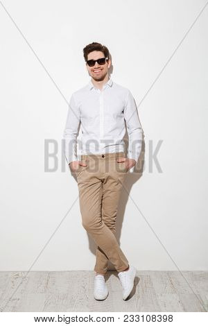 Full length photo of handsome guy dressed in casual clothing and sunglasses smiling while standing with hands in pockets and looking on camera over white wall with shadow