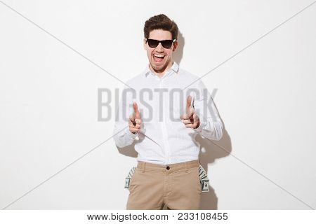 Perky man in black sunglasses pointing index fingers on camera with lots of money dollar bills sticking out from pockets isolated over white background with shadow