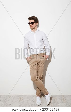 Full length picture of modern calm guy dressed in casual clothing and sunglasses posing on camera with hands in pockets over white background with shadow
