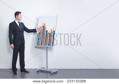 Businessman Delivering Presentation On Business In Simple Concrete Room Interior With Sketch On Whit