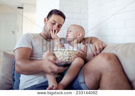 Father And Son Watching Television While Eating Popcorn