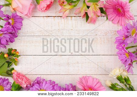 Frame Of Pink And Purple Flowers With Rose, Carnations, Lilies And Daisies Against A White Wood Back