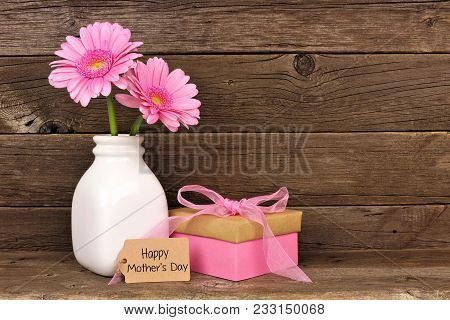 Happy Mothers Day Tag With Gift Box And Vase Of Pink Flowers Against A Rustic Wood Background
