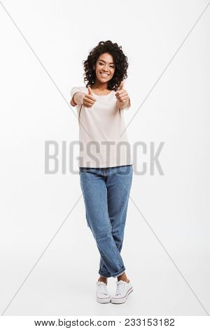 Full length portrait of gorgeous american woman wearing jeans and t-shirt smiling and gesturing thumbs up isolated over white background
