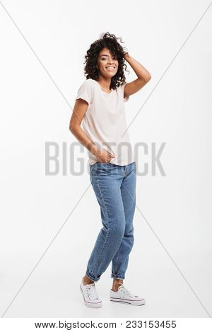 Full length portrait of beautiful american woman wearing jeans and t-shirt posing on camera with candid smile and hand in pocket isolated over white background