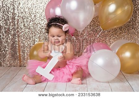 A One Year Old, Baby Girl Playing With A Large Block In The Shape Of A Number One. She Is Wearing A