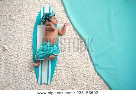 Two Week Old, Alert, Newborn Baby Boy Lying On A Tiny Surfboard. He Is Wearing Aqua Blue, Crocheted