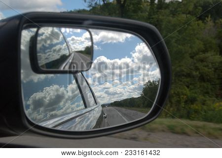 beautiful cumulus clouds in the sky as seen from right side door mirror on a car vehicle, conceptual poster