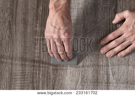 Closeup Of Male Carpenter Sticking Self-adhesive Wooden Film