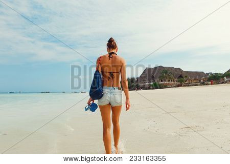 View From Back Young Woman With A Backpack Walking Along Ocean Shoreline Morning At Dawn