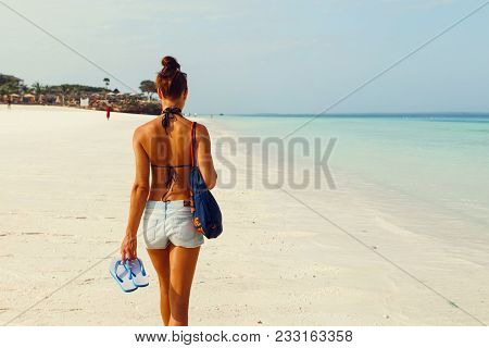 View From Back Young Woman With Backpack Walking Along Ocean Shoreline In The Morning