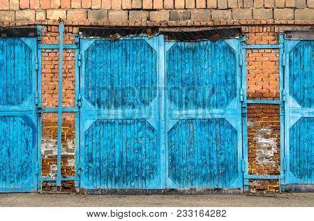 Old, Blue, Skewed Garage Doors On A Collapsing Brick Wall