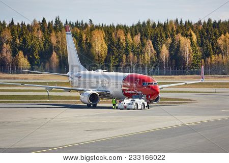 OSLO, NORWAY - MAY 3, 2015: Airliner of Norwegian Air Shuttle taxiing at Oslo Gardermoen airport. Pushed back by towtruck