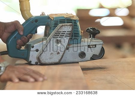 Soft Focus Shot Of Belt Sander On A Piece Wood With Hands Of Worker. Selective Focus And Shallow Dep