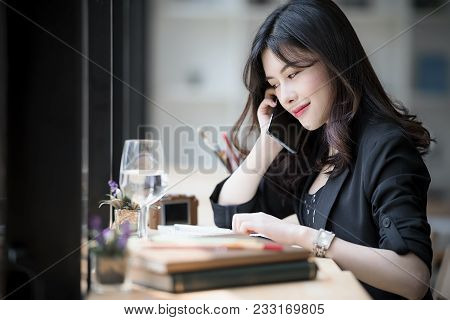 Young Asian Business Woman In Black Suit Using Smartphone While Sitting In Coffee Shop